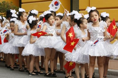 School girls hold Vietnamese and South Korean flags while waiting for arrival of South Korean President Moon Jae-in before a welcoming ceremony at the Presidential Palace in Hanoi, Vietnam (March 23, 2018). Image Credit: Kham/Pool Photo via AP